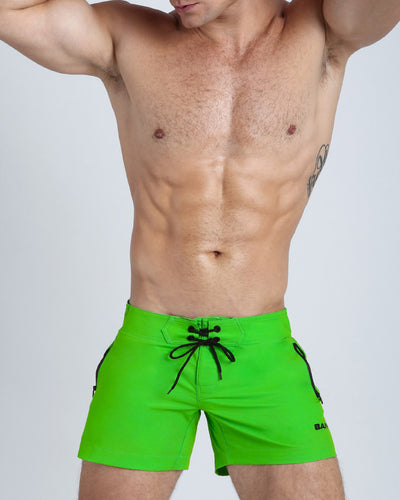 Frontal view of a sexy male model wearing men's beach shorts in bright green lime color by the Miami Bang! Menswear brand.