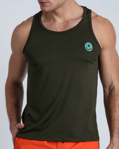 Frontal view of a sexy male model wearing men's tank top in army green color by the Bang! Menswear brand from Miami.