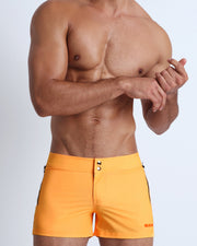 Left side view of a masculine model wearing men's swim shorts In a light  sunrise orange with official logo of BANG! Brand in darker blue shade.