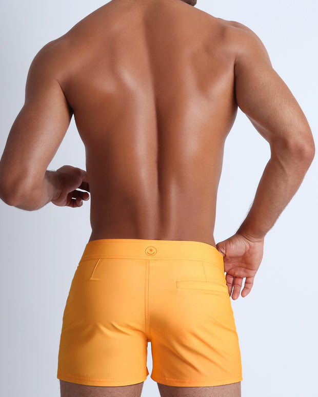 Back view of a male model wearing men's beach trunks in a light sunrise orange by the Bang! Clothes brand of men&