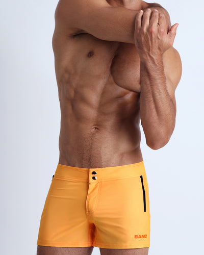 Frontal view of a sexy male model wearing men's beach shorts in a light sunrise orange color by the Bang! Menswear brand from Miami.