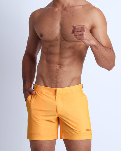 Frontal view of a sexy male model wearing men's tailored shorts in a light sunrise orange color by the Bang! Menswear brand from Miami.