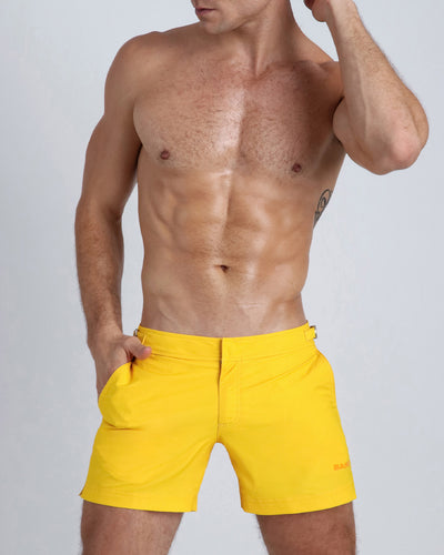 Frontal view of a sexy male model wearing men's beach shorts in yellow by the Bang! Menswear brand from Miami.