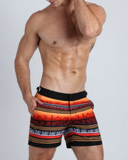These men's tailored shorts show a silhouette of a beach shoreline town in warm tones of orange and browns