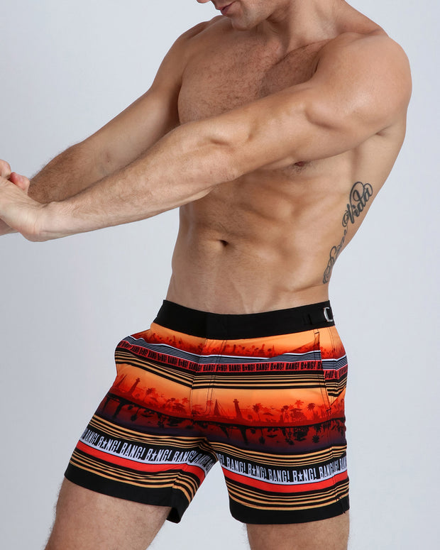 Left side view of a hot male model wearing men's tailored boardshorts by Miami-based Bang! Men&