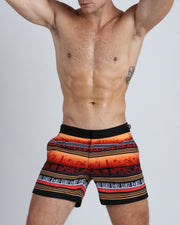 This men's tailored bathing suit shows a silhouette of a beach shoreline town in warm tones of orange and browns