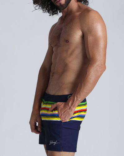 STRIPE'A'POSE DUB Tailored Shorts by Bang Clothes line of Men Swimwear, Swimsuits and beachwear, featuring original print in dark blue, with progression of color srtipes in yellow, red and green.