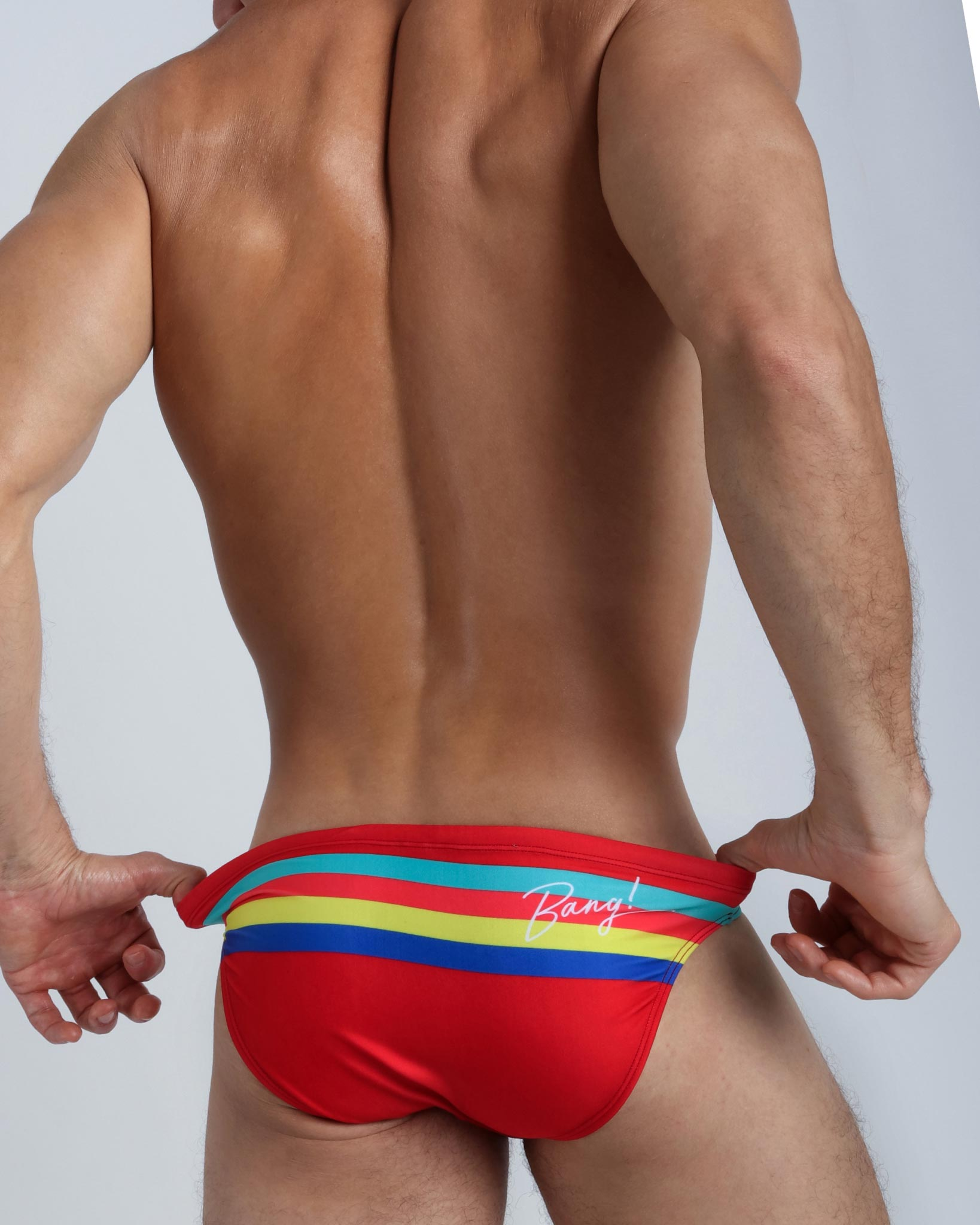 Right side view of a model wearing red men's bikini swimsuit with color stripes in aqua green, bold red, yellow and blue.