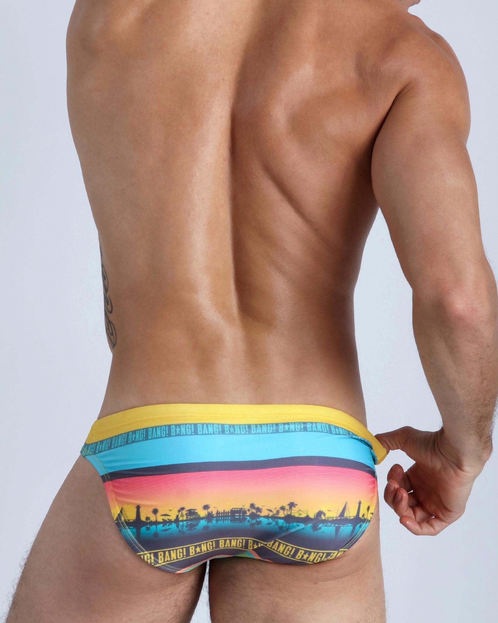 Back view of a male model wearing men's swim mini-brief in bold yellow by the Bang! Clothes brand of men's beachwear.
