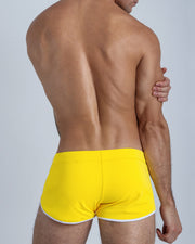 Back view of a male model wearing men's swim shorts in bold yellow by the Bang! Clothes brand of men's beachwear.