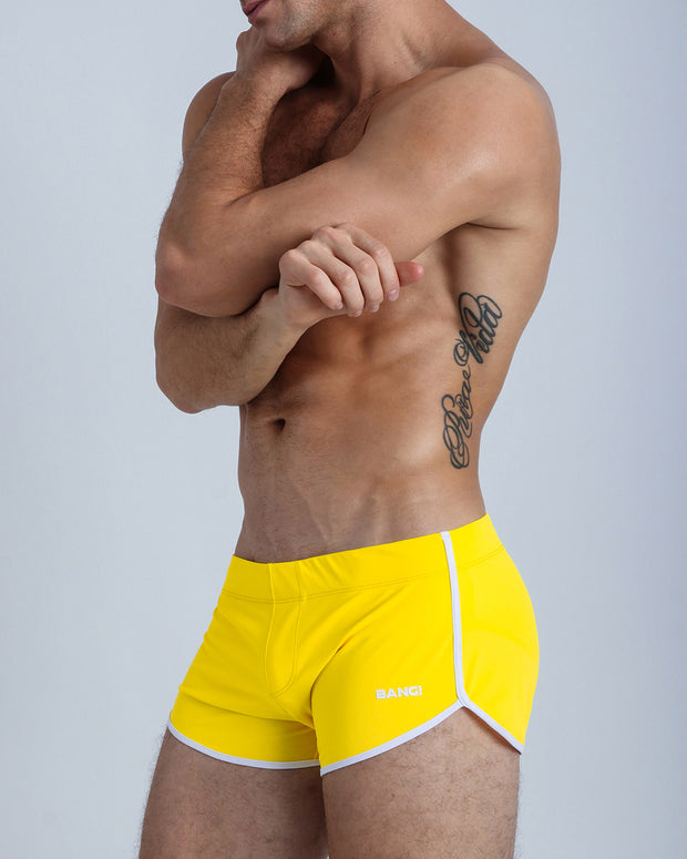 Left side view of a masculine model wearing men's swimsuit in brigh yellow with official logo of BANG! Brand in white.