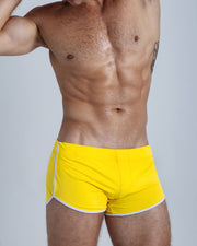 Right side view of an in shape men wearing swim trunks in solid yellow by the Bang! brand of men's beachwear from Miami.