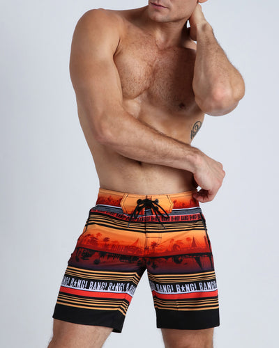 These men's boardshorts show a silhouette of a beach shoreline town in warm tones of orange and browns