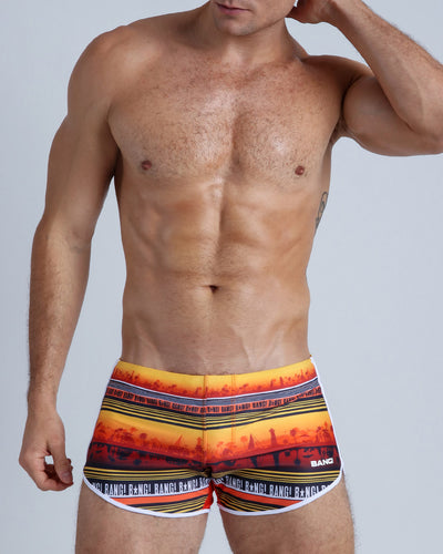 This men's bathing suit shows a silhouette of a beach shoreline town in warm tones of orange and browns