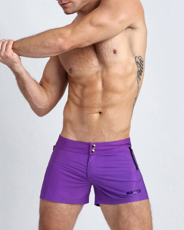 Left side view of a masculine model wearing men's swim shorts in purple violet color with official logo of BANG! Brand in darker purple shade.