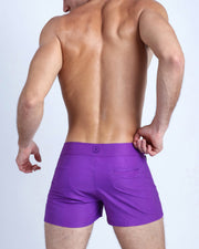 Back view of a male model wearing men's beach trunks in purple violet color by the Bang! Clothes brand of men's beachwear from Miami.