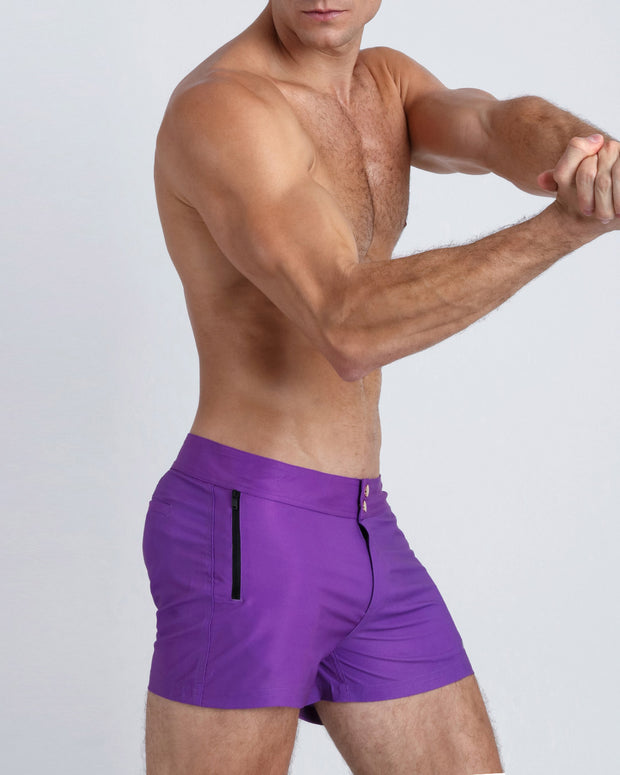 Right side view of an in shape men wearing boardshorts in purple violet color by the Bang! Clothes brand of men&