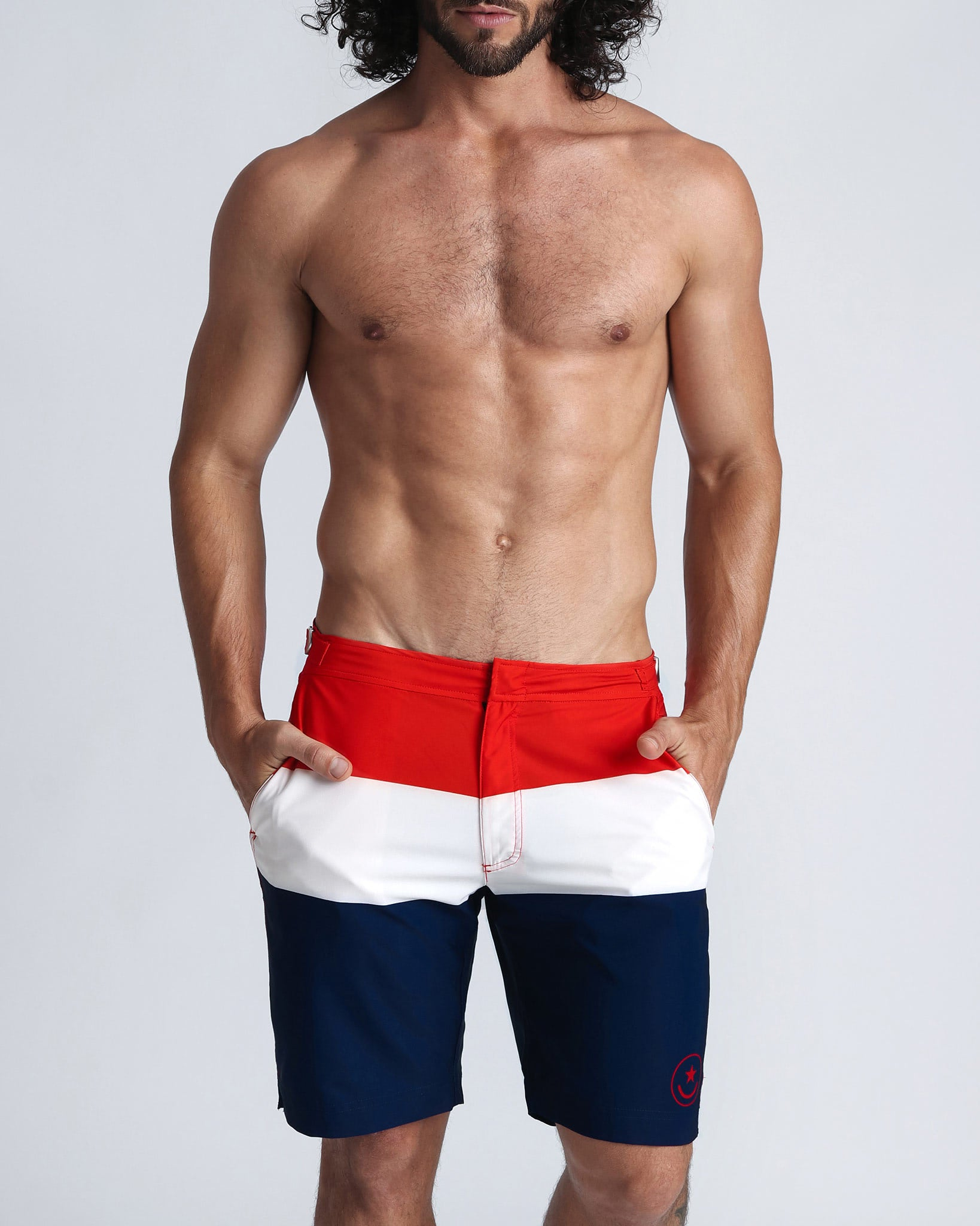 TRIAD Tailored Boardshorts (long leg, but right above knees) by Bang Clothes line of Men Swimwear, Swimsuits and beachwear, featuring original print with three main bold colored stripes, in red, white and blue, similar to matching tones of national flags of countries such as United States, France, United Kingdom, Australia, and many more.