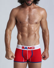 Frontal view of a sexy guy wearing a men's premium cotton boxer brief in red with white waistband and BANG! brand logo.