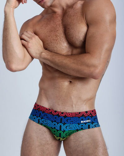 These men's swimsuit features a pattern of the BANG! name repeated in rainbow-like colors placed against black.