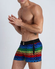 These men's beach shorts feature a pattern of the BANG! name repeated in rainbow-like colors placed over a black backgound.
