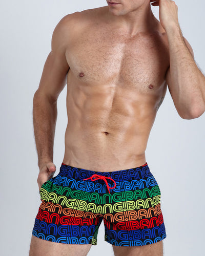 These men's beach trunks feature a pattern of the BANG! name repeated in rainbow-like colors placed over a black backgound.