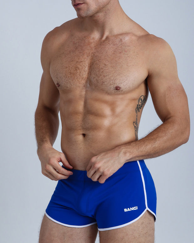 Left side view of a masculine model wearing men's swimsuit in midnight blue with official logo of BANG! Brand in white.