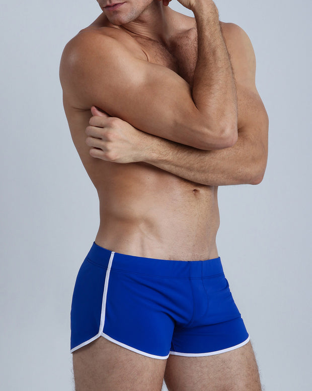 Right side view of an in shape men wearing swim trunks in navy blue by the Bang! Clothes brand of men&