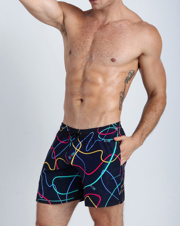 Left side view of a hot male model wearing men's resort shorts by the Bang! Clothes menswear brand from Miami.