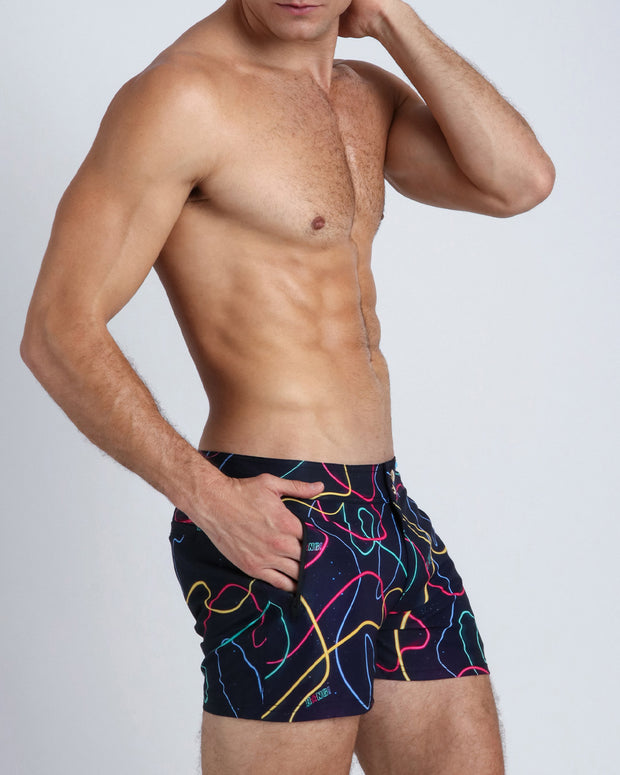 Left side view of a hot male model wearing men's swim trunks by the Bang! Clothes menswear brand from Miami.
