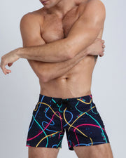 Frontal view of a sexy male model wearing men's beach shorts by the Bang! Clothes brand of men's beachwear from Miami.