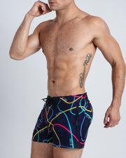 Left side view of a hot male model wearing men's flex shorts by the Bang! Clothes menswear brand from Miami.