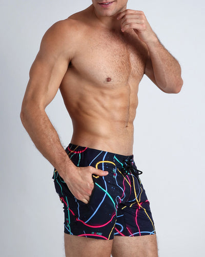 These men's beach shorts show strings of neon lights in pink, yellow, blue and green, against a black background with stars.