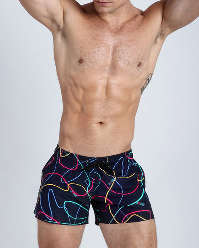 Frontal view of a sexy male model wearing men's beach shorts made by the Bang! Clothes brand of men's beachwear from Miami.