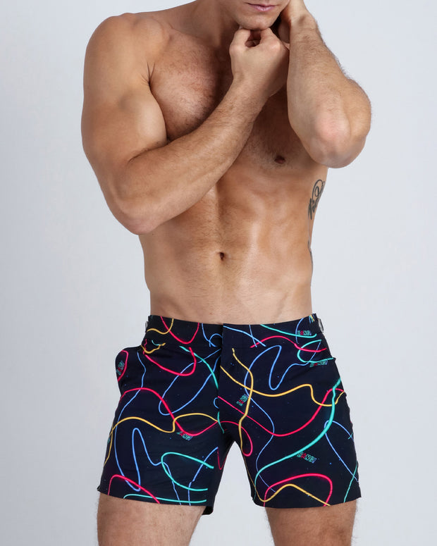 Frontal view of a sexy male model wearing men's beach tailored shorts by the Bang! Clothes brand of men&