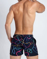 These men's tailored shorts show strings of neon lights in pink, yellow, blue and green, against a dark stared background.