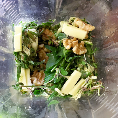 blender for making pesto, with arugula leaves and flowers, cheese, and walnuts