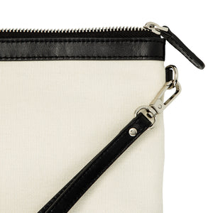 Close up of canvas and leather wristlet bag with inbuilt phone charger showing silver hardware.