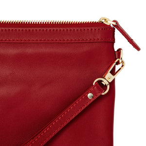 Close up of red leather wristlet bag with inbuilt phone charger showing gold hardware.