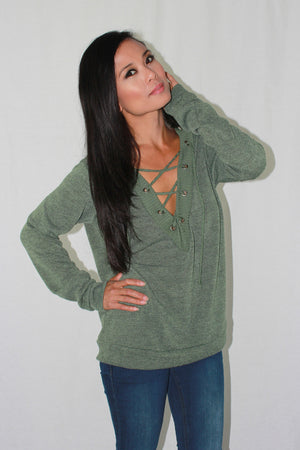 Knit top with lace up neckline in green. 2