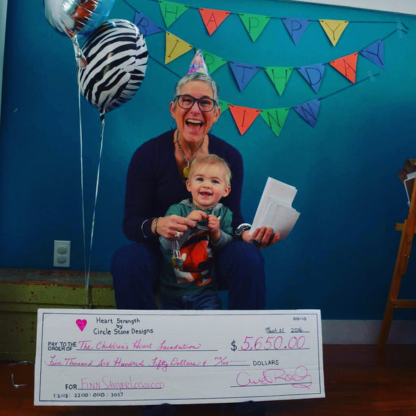 Celebrating Finn's birthday with check to support The Children's Heart Foundation