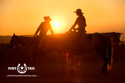 cowgirls on horseback with sunset guest ranch