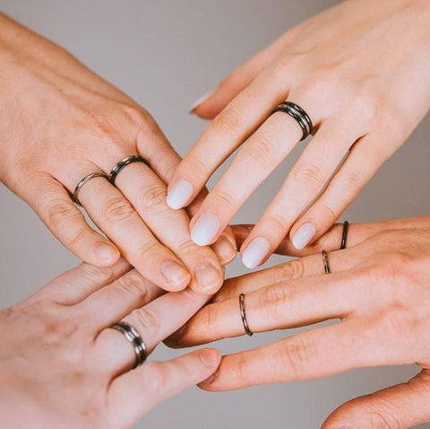 Four hands touching with stackable rings pairings