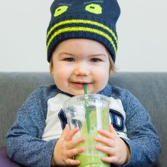 child drinking green smoothie