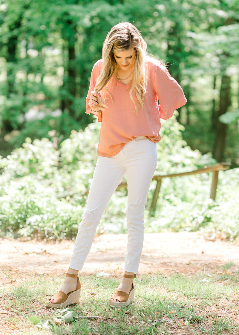 model wearing a salmon colored top - epiphany boutiques