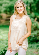 model in a sleeveless cream top - epiphany boutiques