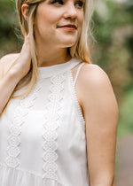 model wearing a white  top with applique lace - epiphany boutiques