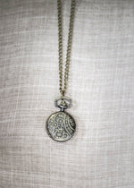 Back etching detail of 1 inch bronze tone roman numeral pocket watch on 30 inch chain by two tree design