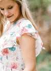 model in a floral top with ruffle sleeves - epiphany boutiques