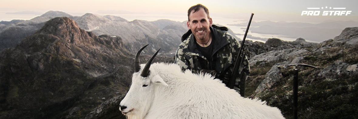 John Nores Jr. on a mountain top with a goat